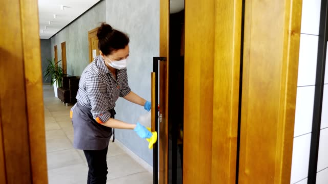 female cleaning lady, in protective mask and gloves, wipes door handles with antiseptic in restaurant or public establishment. protection against coronavirus, safety concept video