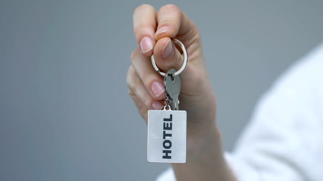 Female client clenching keychain with hotel word, luxury service, friendly stuff