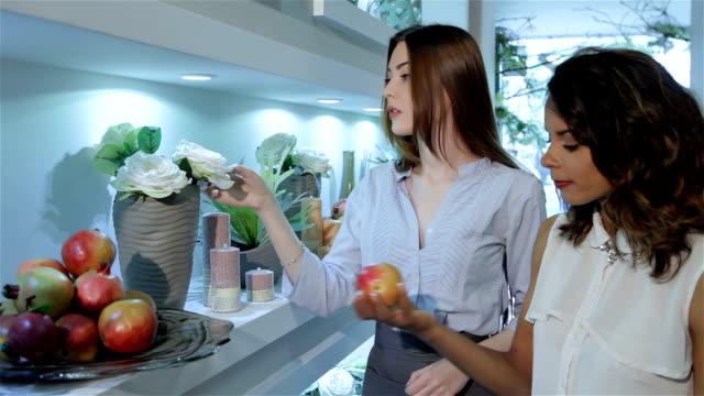 Female client take the garnet from flower shelf video