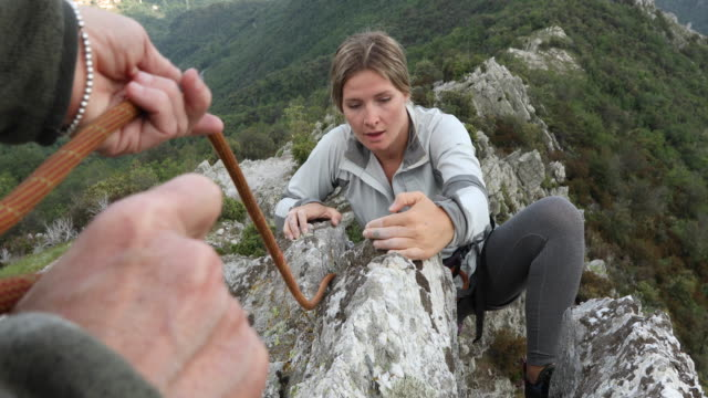Female climber ascends rock ridge above valley, mountains