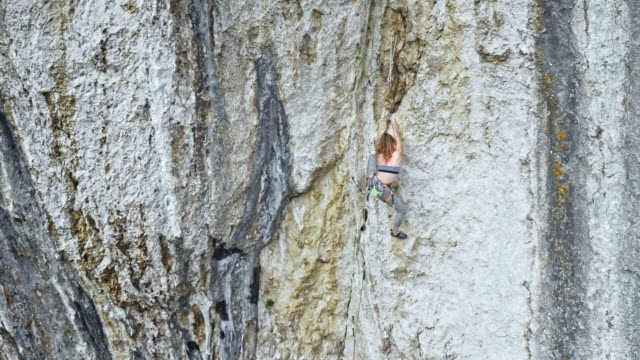 AERIAL Female climber climbing up a white cliff