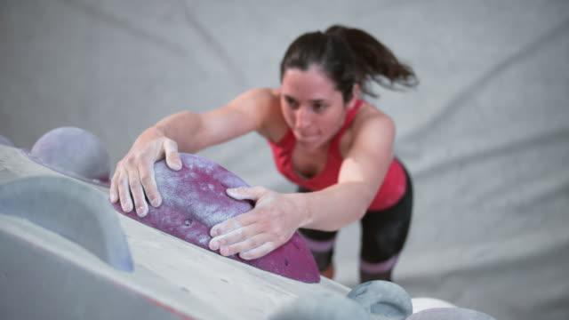 vidéos et rushes de slo mo ld grimpeur femelle suspendu sur une cale dans une salle de gym intérieure de rocher - courage