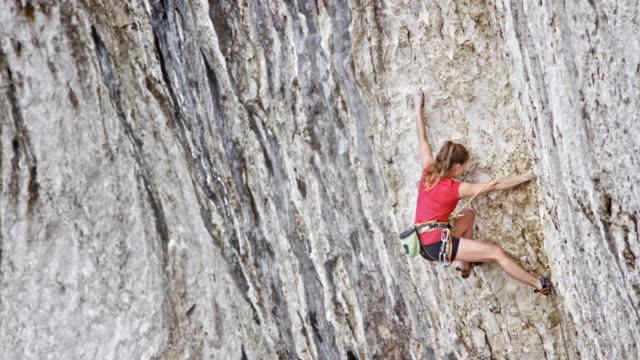 vídeos y material grabado en eventos de stock de trepador mujer en camisa roja ascendente un acantilado - escalada en rocas