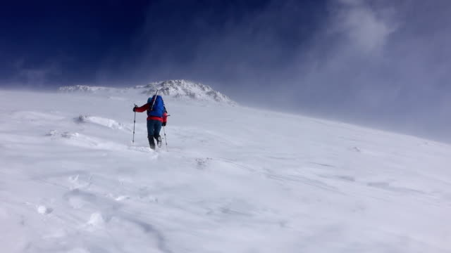 female climber in the snow storm on high attitude video