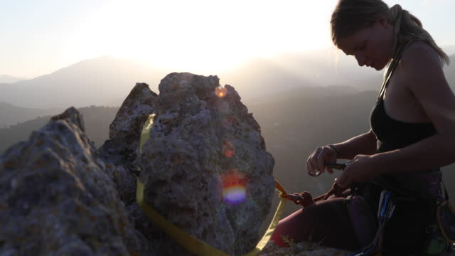 female climber organizes rope and gear on summit, at sunrise - pantaloni capri video stock e b–roll