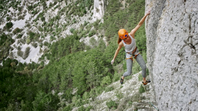 Female climber positioning the quickdraw and clipping the rope video