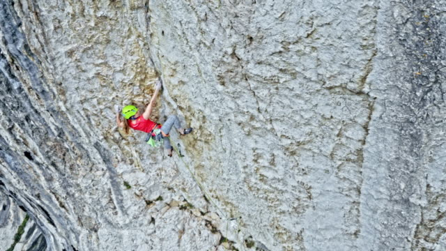 AERIAL Female climber pulling her rope through the quickdraw while standing in the cliff video