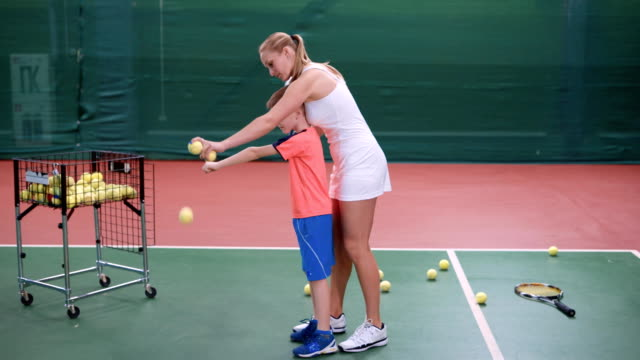 Female coach dressed in short white sport dress is teaching little boy to play at indoor court. Professional tennis instructor is showing to male toddler process of returning a ball with racket video