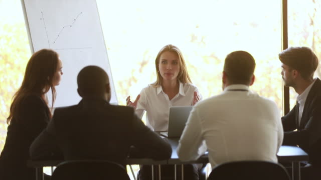 Female coach talking at group office meeting sit at table
