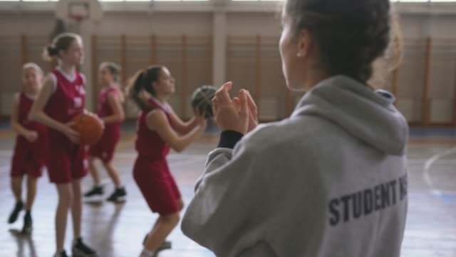 Female coach watching teenage girls practicing free throws Rear view of young female basketball coach watching and cheering teenage girls while practicing free throws at sport court high school sports stock videos & royalty-free footage