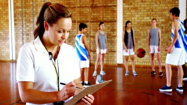 Entraîneure, écrivant sur presse-papiers tandis que des étudiants jouant au basket - Vidéo