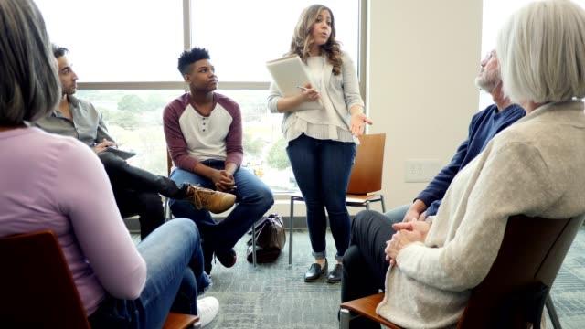 il rappresentante del college femminile parla con un gruppo di persone del processo di ammissione al college - comunità video stock e b–roll