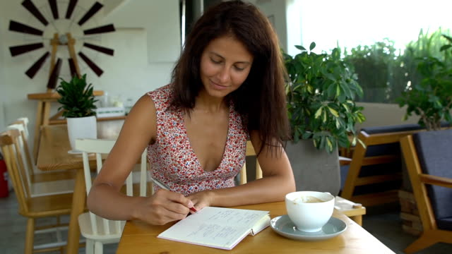 Female college student writing in notepad with pen video