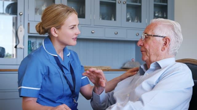 vídeos y material grabado en eventos de stock de mujer comunidad enfermera visitante senior hombre en casa - servicios sociales