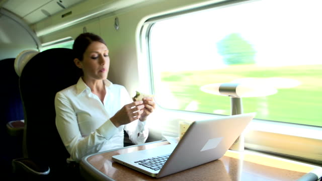 Female Commuter On Train Using Laptop Whilst Eating Sandwich video