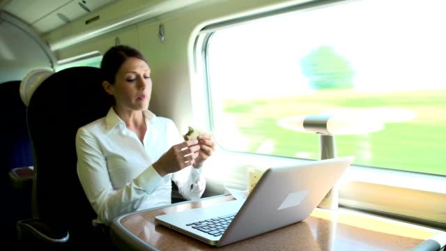 Femme en Train de banlieue à l'aide d'un ordinateur portable tout en mangeant un Sandwich - Vidéo