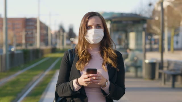 female commuter with a protective medical face mask in the city - mascherina video stock e b–roll