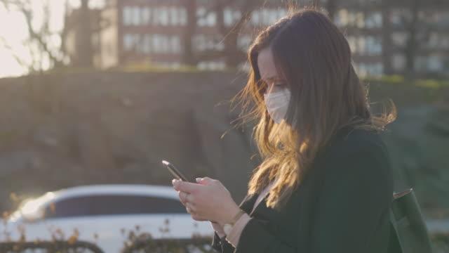 Kvinnlig pendlare med skyddande medicinsk ansiktsmask i staden video