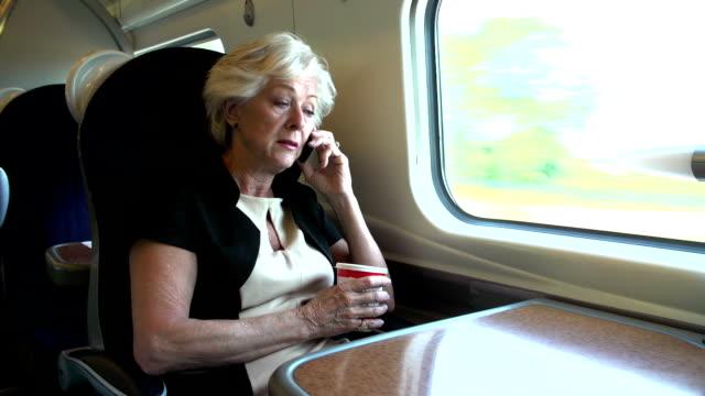 vídeos y material grabado en eventos de stock de mujer en tren suburbano con café mediante teléfono móvil - viaje en primera clase