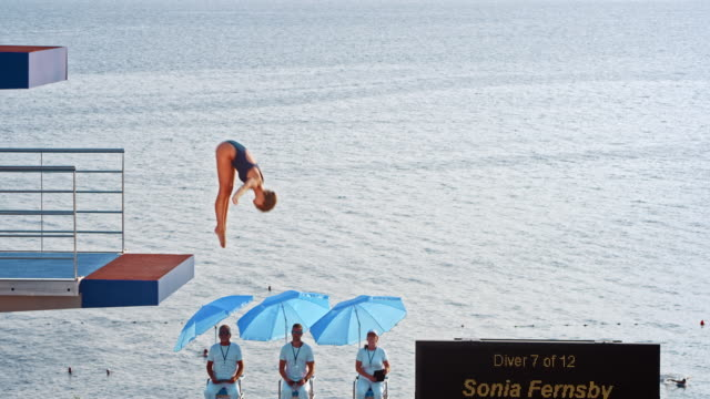 slo mo female competitor diving into the pool from a sunny diving platform - sky diving video stock e b–roll