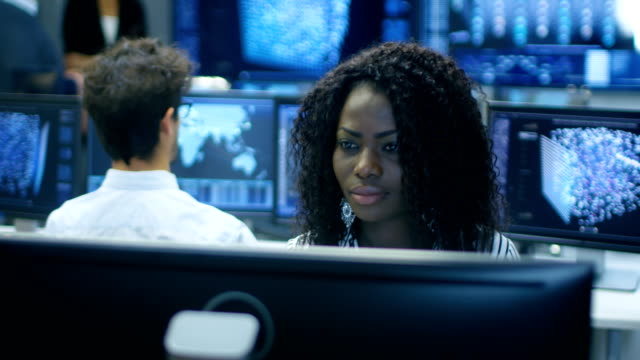 Female Computer Engineer Works on a Neural Network/ Artificial Intelligence Project with Her Multi-Ethnic Team of Specialist. Office Has Multiple Screens Showing 3D Visualization. video