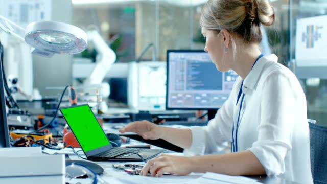 Femme ordinateur scientifiques Connects Circuit Board à son ordinateur portable et commence de programmation il. Elle travaille dans le laboratoire technologiquement avancé. - Vidéo