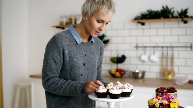 vidéos et rushes de confiseur femelle dans sa cuisine avec soi fait des muffins et gâteaux. envie de pâtisserie décorée sur la table. slow motion - boulanger