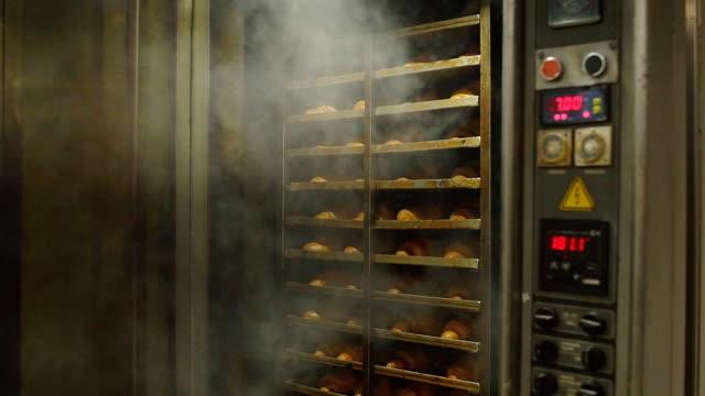vidéos et rushes de une confiseur ouvre le four avec des croissants de pâtisseries fraîches. industrie de la confiserie et de la boulangerie, ralenti - pâtisseries et feuilletés