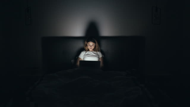 Female connected online at late hours.