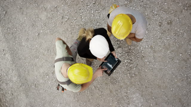 vidéos et rushes de coordinateur de construction cs femelle sur le chantier, tenant une tablette numérique et passant par les plans avec deux ouvriers - chantier