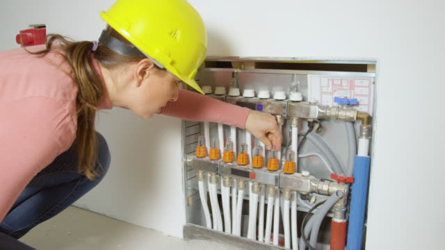 CLOSE UP: Female contractor wearing a hard hat checks the heating system valves.