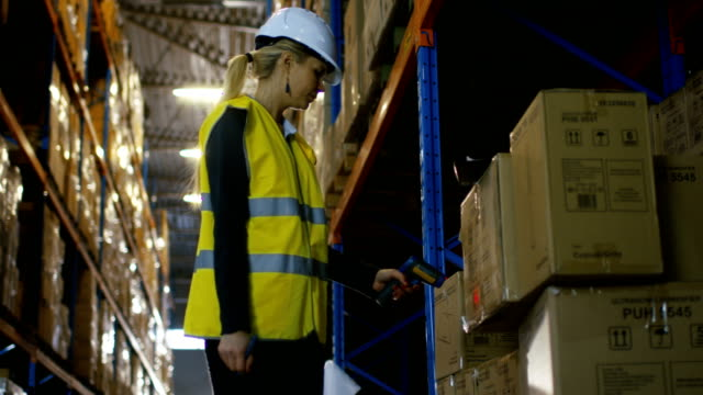 Female Controller Wearing Hard Hat and Scans Merchandise with Bar Code Scanner. She's in a Big Warehouse Full of  Pallet Racks. video
