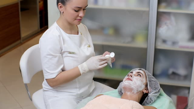 Female cosmetologist making cosmetic facial mask to the female client at the cosmetology centre. Close up of pretty caucasian girl blinking while cosmetologist smearing cosmetic treatment on her face video