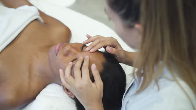 Female cosmetologist massaging face of african woman in spa salon