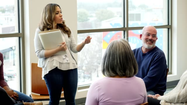 vídeos de stock e filmes b-roll de female counselor leads support group meeting - liderança