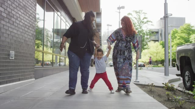 Female Couple Walking with Their Son A homosexual biracial female couple walks with their young boy down a city street. One woman is Caucasian and the other is African-American lesbian stock videos & royalty-free footage