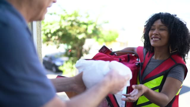 kadın kurye onun ön kapıda kıdemli adama yiyecek teslim - sahanlık stok videoları ve detay görüntü çekimi