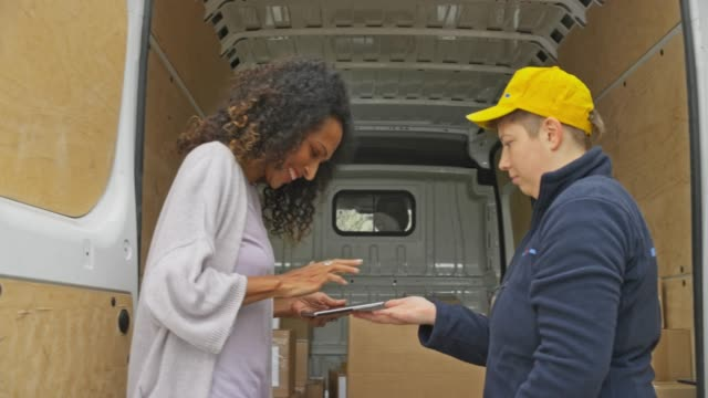 Female courier giving the smiling woman a POD to sign before handing her the package