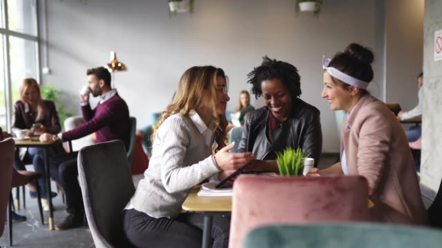 Female coworkers taking a coffee break in cafe Group of Three multi-ethnic female friends drinking coffee in cafeteria, using smart phone and laughing cafeteria stock videos & royalty-free footage