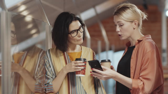Female Coworkers Using Smartphone and Talking on Coffee Break