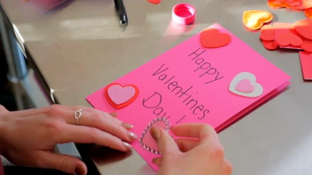 Une femelle créant une carte Happy Valentines Day avec qui dit que t'aime - Vidéo