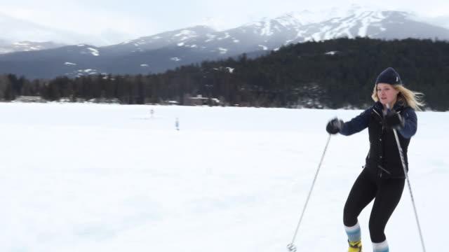 female cross country skier traverses lakeshore course - sci sci e snowboard video stock e b–roll