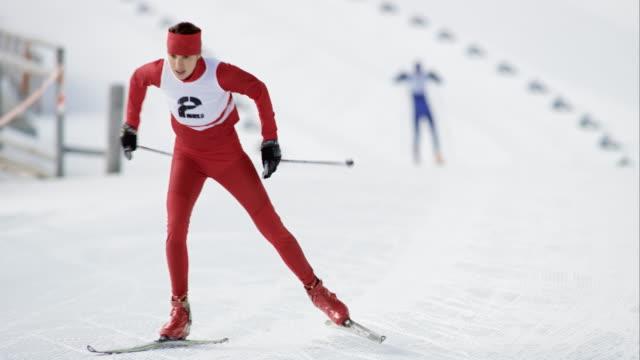 vídeos de stock e filmes b-roll de slo mo female cross country skiing athlete in sprint - campeonato