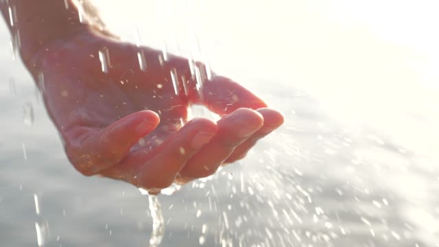 female cupped hand catches falling water drops on seascape background. the sun sparkles on woman hand, while drops of water falling on the palm. woman hand playing with drink water drops - stan naturalny filmów i materiałów b-roll