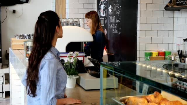 Female Customer And Barista At Cafe Counter video