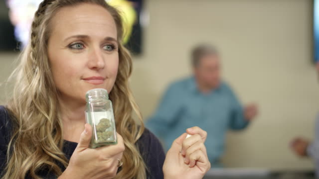 Female customer at a marijuana shop smelling a product and smiling video