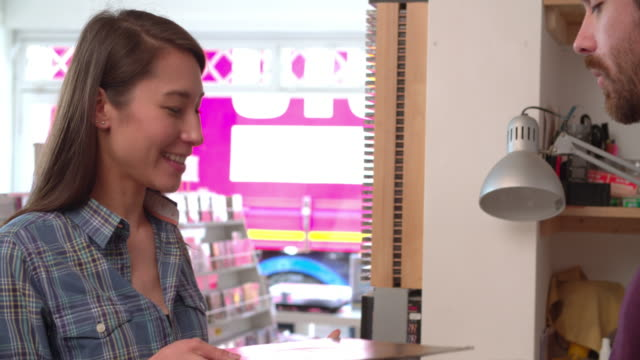 Female customer being served at the counter of a record shop video