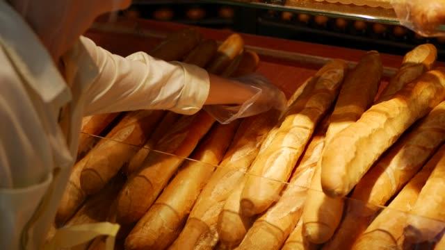 female customer buying fresh baguette in bakery - pane forno video stock e b–roll