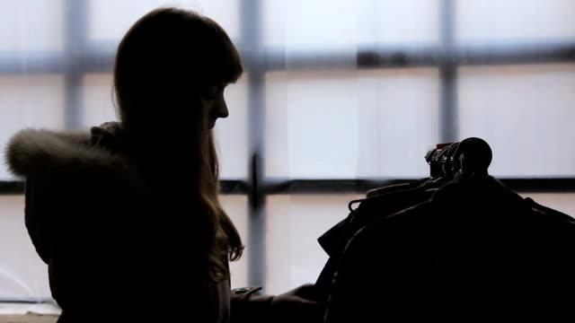 vídeos de stock, filmes e b-roll de escolha roupas de cliente feminino no mercado de fabrico local, silhueta - arméria