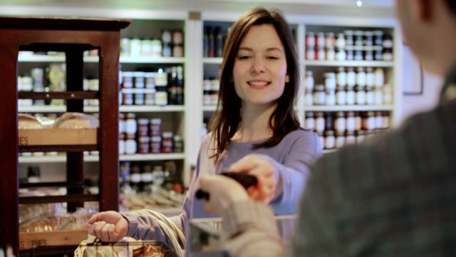 female customer paying sales assistant for shopping in delicatessen with contactless credit card - contactless payment stock videos & royalty-free footage